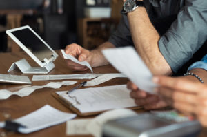 Closeup of people calculating expenses with receipts and pen and paper