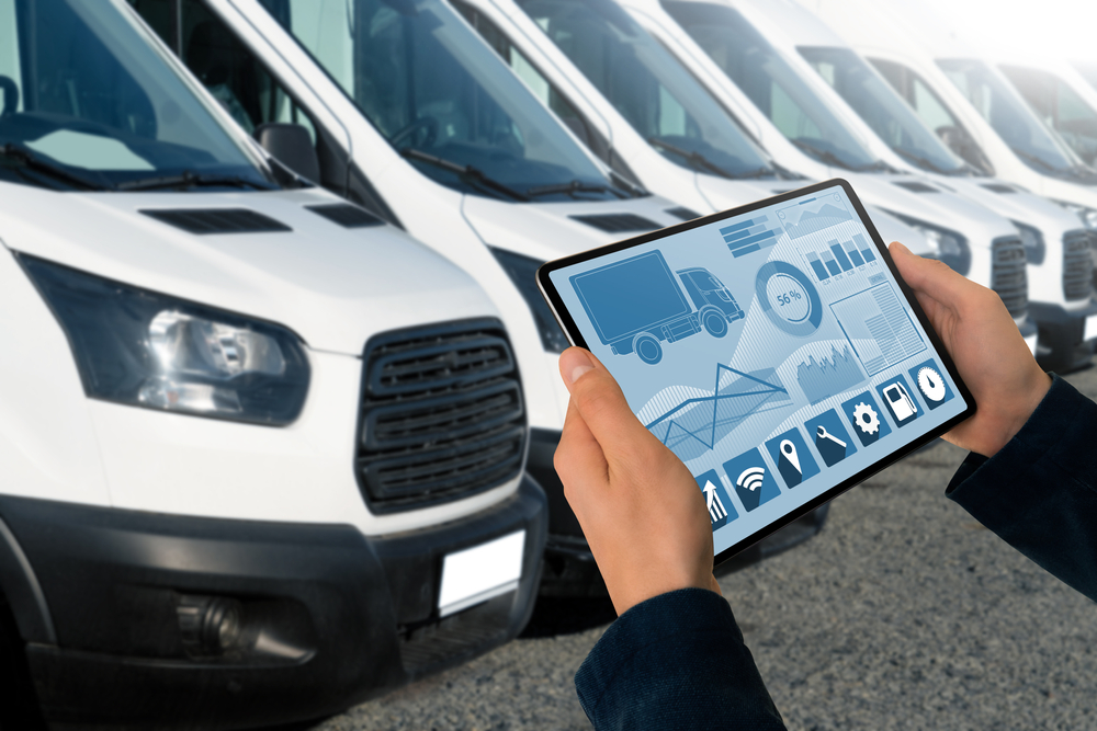 Man with tablet displaying data in front of fleet of vans