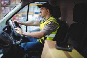 Image of a delivery driver at the wheel of a van, with a parcel in the foreground on a seat