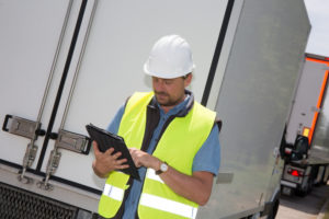 A driver records information on a tablet near an HGV.