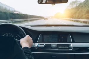 Dashboard view of person driving a car down motorway