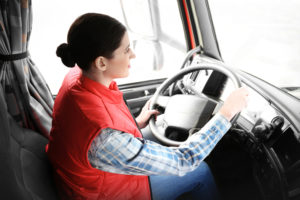 Young female driver sitting in cab of truck