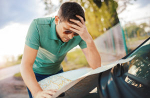: Image of a man reading a map on the bonnet of a car