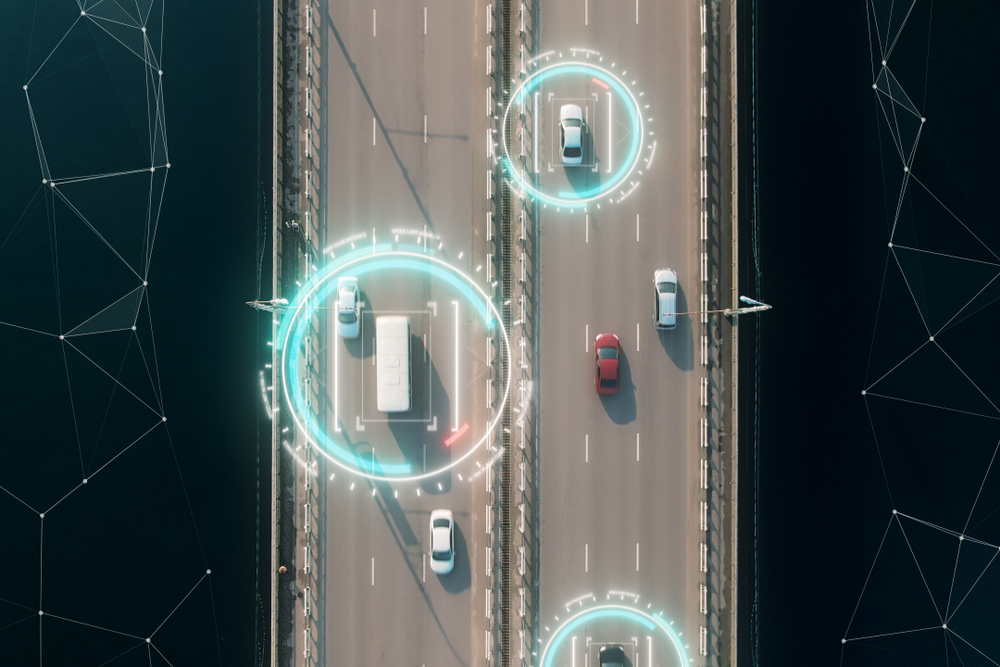 Overhead view of vehicles on a motorway with digital tracking overlay.