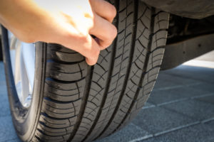 Close-up of hands checking the tread of a car tyre