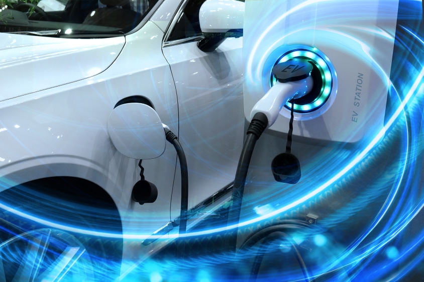 White electric car with charger plugged in, blue graphics to indicate power