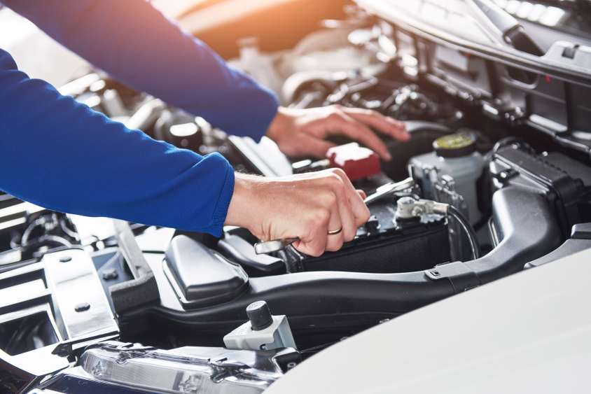 Hands of mechanic with wrench working on car engine