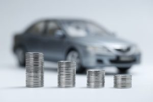 Silver coins stacked in front of grey toy car