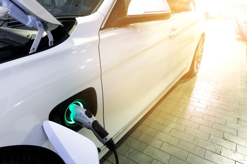 White electric car plugged into charge point