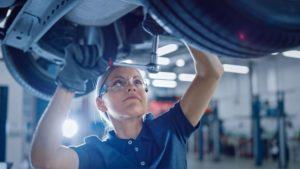 A female mechanic works underneath a vehicle