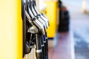 Fuel nozzles lined up at yellow fuel pumps