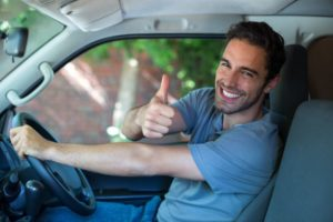A smiling man driving a van gives a thumbs up