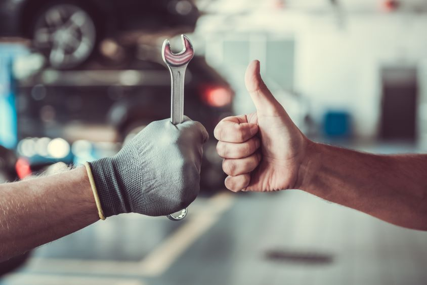 Two arms are shown. One gives a thumbs up, the other holds a spanner.