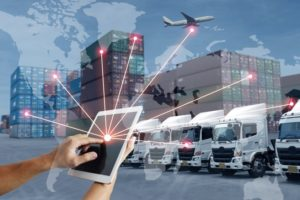 Hands on iPad with telematics graphics connecting a fleet of lorries and a plane