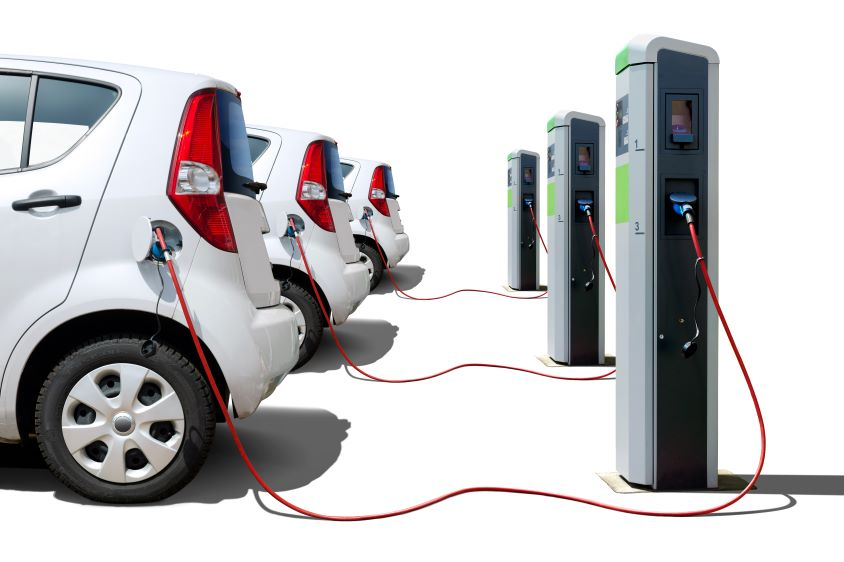 3 white electric cars in a row, each connected to a charging point