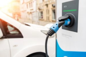 Electric vehicle charging point with blue nozzle next to a parked electric car