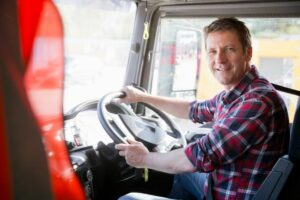 Male HGV driver smiling in the vehicle cabin