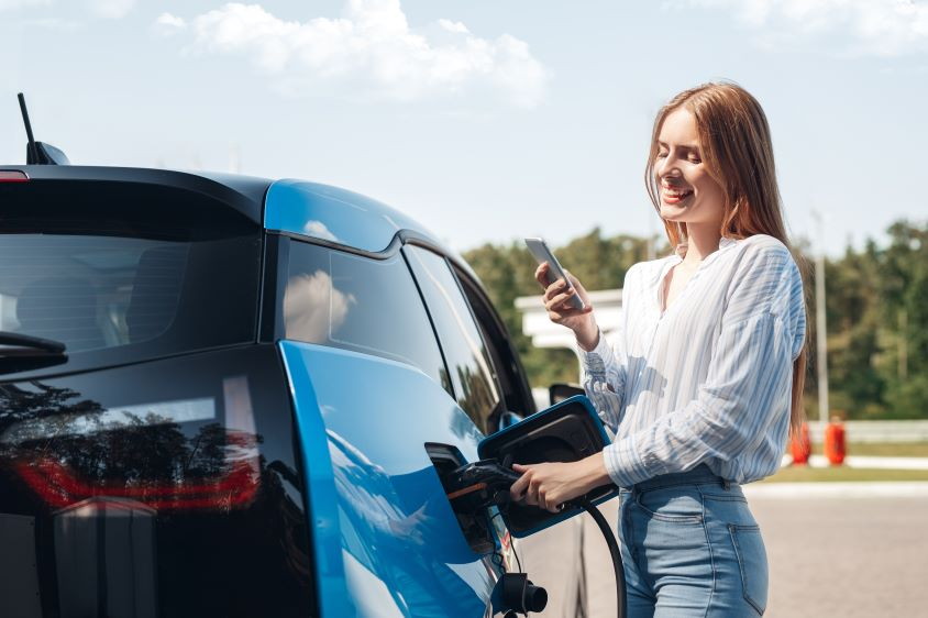 Woman standing next to blue car whilst it charges, looking at her phone