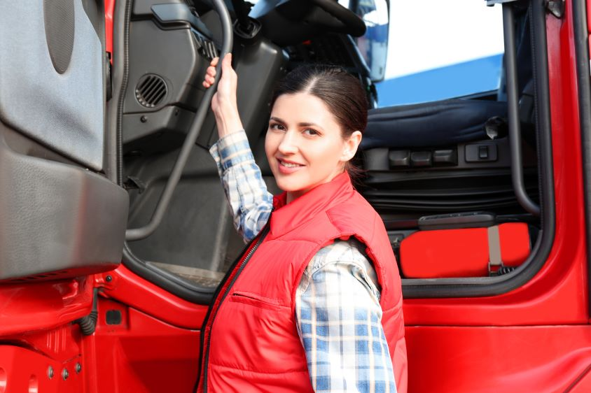 A female HGV driver standing next to the door of a red truck