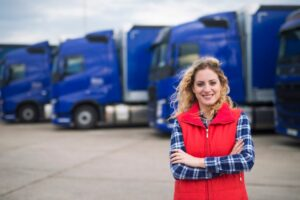 Female truck driver in red gilet standing in front of a row of blue HGVs
