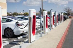 Row of white Tesla electric cars charging at a station