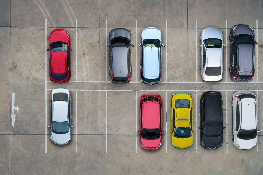 An aerial view of cars in parking spaces