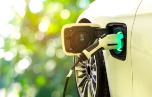 A picture of an electric car with its cable plugged in