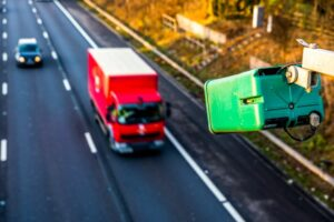 Green average speed camera pointed at red lorry driving on motorway