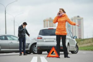 Warning triangle placed on road whilst woman is on the phone after car accident