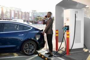 Man stood next to electric car whilst it charges