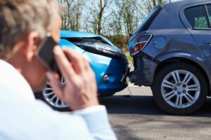 Man holds phone to ear whilst looking at a car accident