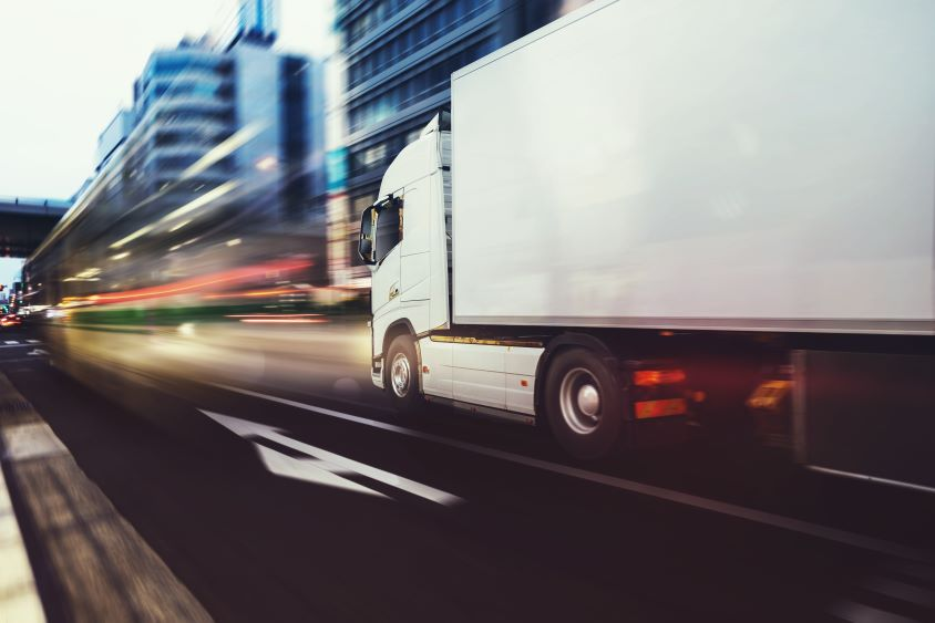 Lorry driving towards city with blurred lights to indicate speed
