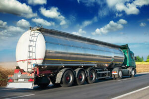 Tanker driving on road next to field, shipping a large tank