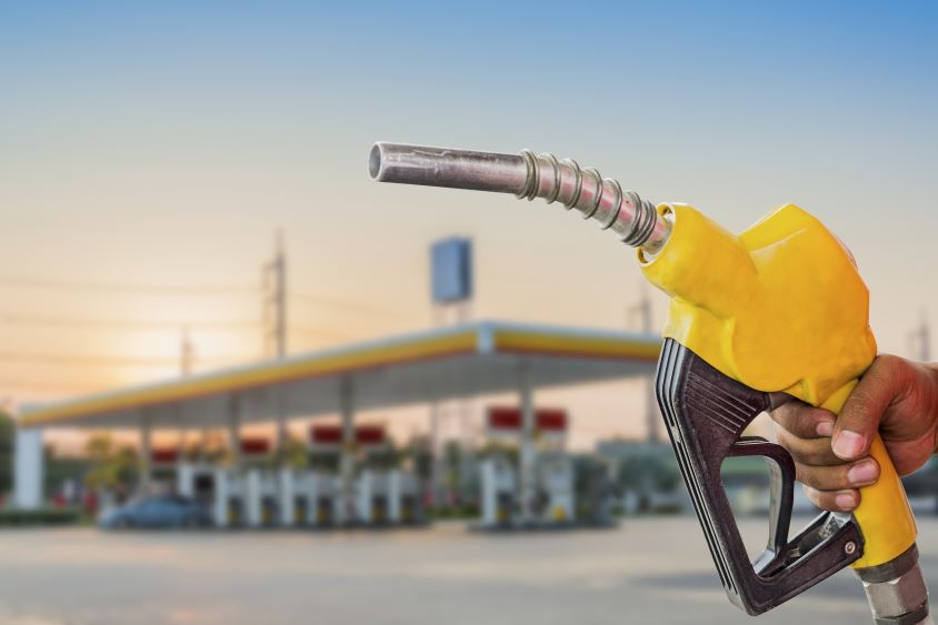 Hand holding yellow fuel nozzle in front of fuelling station
