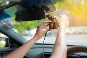 Female hands adjusting a dash cam in the interior of a car