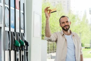 Smiling man holds up fuel card next to fuel pumps