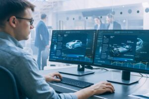 Man sitting at computer with two monitors with car grapbics