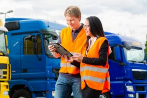 Two HGV drivers in hi-vis jackets looking at tablet