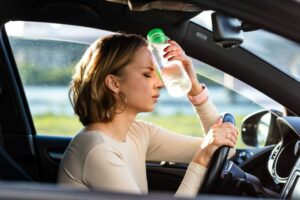 Exhausted woman driving in heat with cold water bottle pressed to forehead