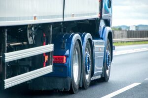 Blue lorry driving along road
