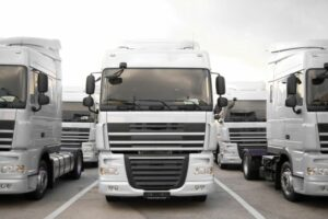Row of white HGVs in a parking bay