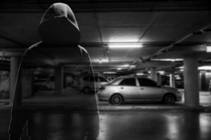 Black and white image of a suspicious hooded man in a car park