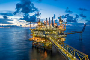 Oil rig at sunset with orange lights