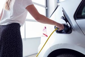 Woman plugging charger into electric vehicle