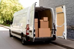 Delivery van with open back doors showing cardboard boxes