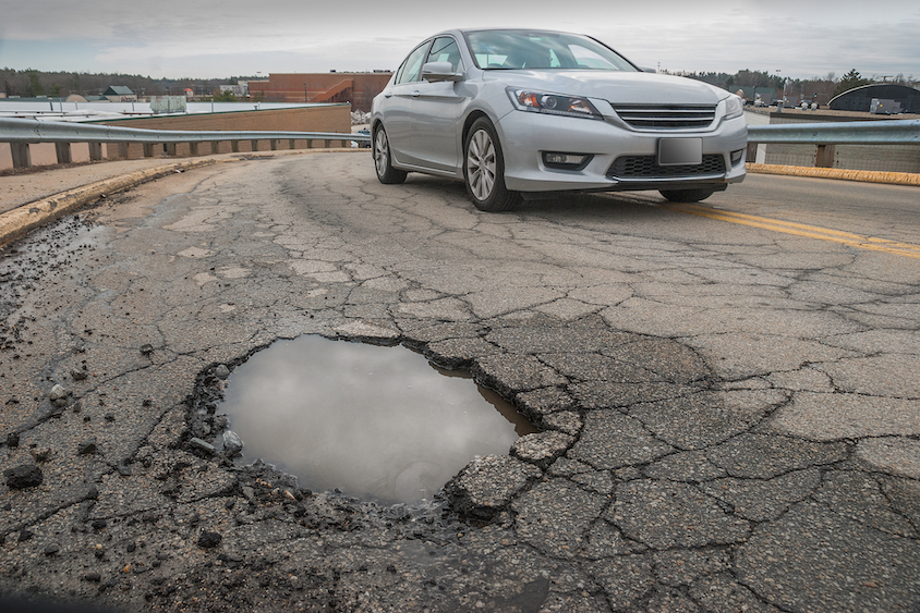 Car avoids large pothole which could cause vehicle damage