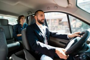 Smiling taxi driver talking to passenger