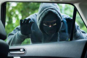 Thief in balaclava peering through car window