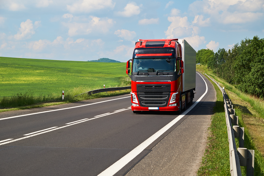 Red lorry on country road