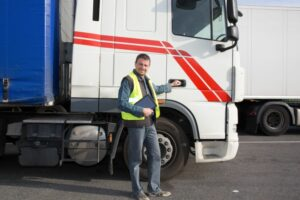 driver in front of hgv holding tablet